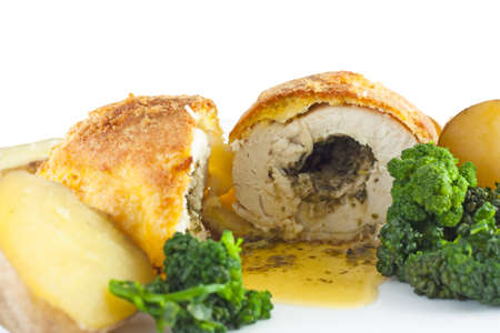 Garlic Chicken Kiev with broccoli and boiled potatioes against a white background