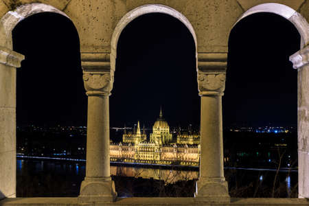 bastion: Hungarian Parliament building shot through the arches of the Fishermans Bastion in Budapest Hungary Stock Photo