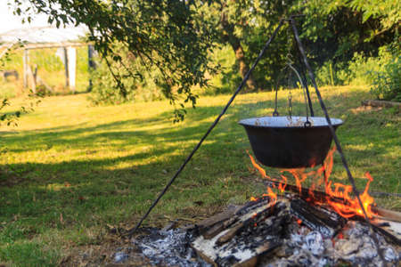 Cooking outdoors over an open fire with a traditional Hungarian cooking pot Stock Photo