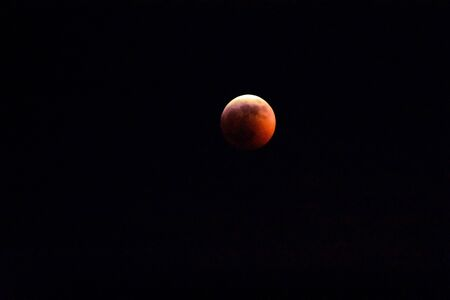 A Photograph of a full red super moon on a black background. Reklamní fotografie - 135465604