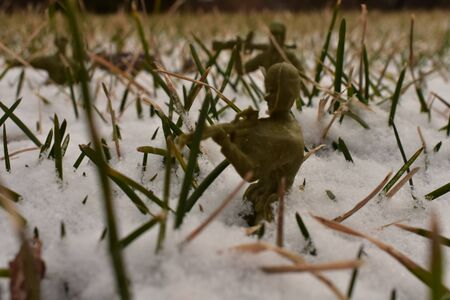 A Close up shot of Toy Army Men marching through the deep snow.