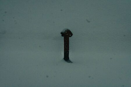 A Photograph of a Chimney Pipe Coming out of a Snow Covered Roof