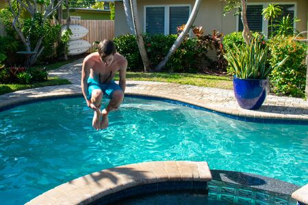 A Shot of a Young Man Jumping into a Pool in a Tropical Location