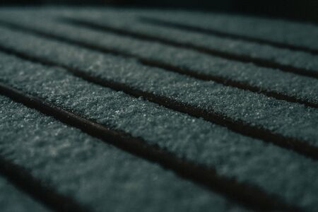 An Image of Fresh Snow Fall taken on a wooden table with small spaces in-between each piece of wood.