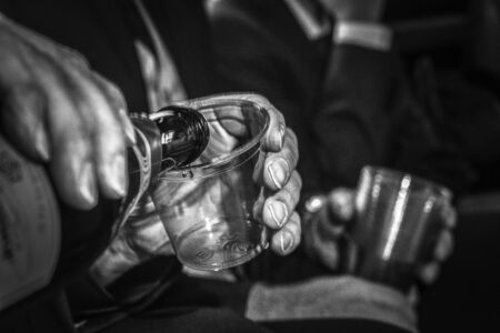 An image of a man pouring champagne into a clear plastic cup while riding in a limousine in Black and White