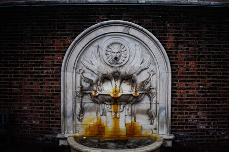 A White Rust Stained Fountain Against a Brick Wall inside a Courtyard. Reklamní fotografie