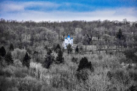 A Shot of a Distant Church Forest Landscape and Skyline With Blue Highlighted