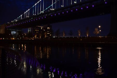 A Photograph of a Suspension Bridge Reflecting Purple Lights off of a River
