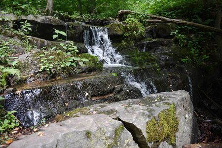 A Photograph of a Waterfall that Flows Over a Small Rock Formation