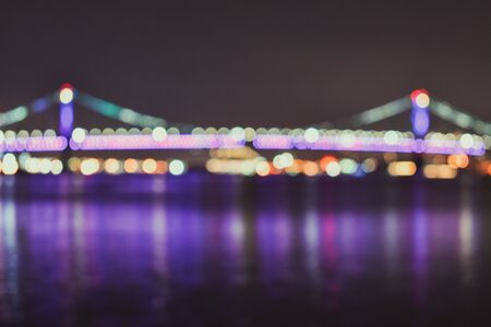 A Blurred Shot of a Bridge Covered in Lights that reflect off the water and cast long purple streaks across it. 스톡 콘텐츠