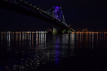 A Beautiful Photograph of the Ben Franklin Bridge, taken at night, from the Race Street Pier. Dark.