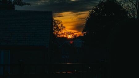A Dark, Orange and Blue, Dramatic Sunset Over a Suburban Neighborhood that is silhouetted