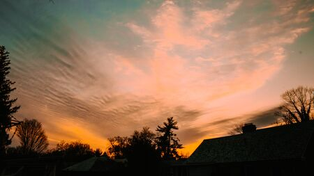 A Dramatic Blue and Orange Cloudscape With Silhouette Trees and a Building towards the bottom of the shot. 스톡 콘텐츠