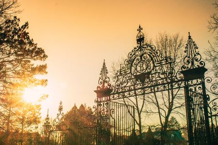 A Shot of a Black Gate at the Entrace of a Gated Community with a Bright Orange Sunset in the Background