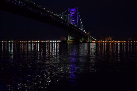 A Beautiful Photograph of the Ben Franklin Bridge, taken at night, from the Race Street Pier. Dark.