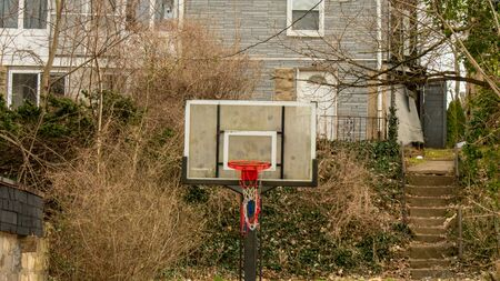 A Red White and Blue Torn Basketball Net With a Red Rim and a Clear Backboard in a run down area