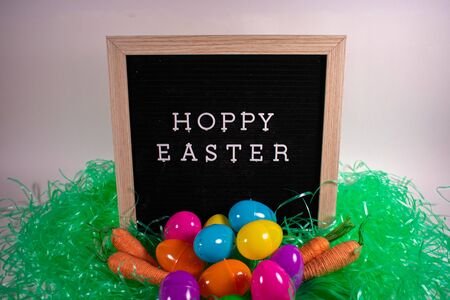 A Black Sign With a Birch Frame and White Letters That Says Hoppy Easter With Green Easter Grass in the Foreground and a Pile of Easter Eggs with String Carrots on Each Side In Front of It