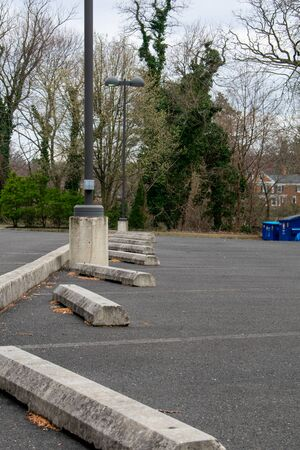 A Row of Parking Stops in a Parking Lot With Trees in the Background