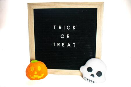 A Black Sign With White Letters That Says Trick or Treat With a Jack o Lantern and Skeleton Plush on a White Background Stok Fotoğraf