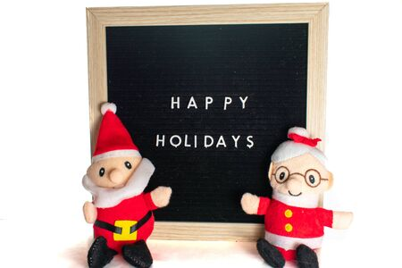 A Black Sign With White Letters in a Birch Frame That Says Happy Holidays With Santa Claus and Mr's Claus in front of it.