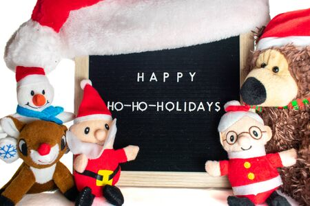 A Black Sign With White Letters in a Birch Frame That Says Happy Holidays With Stuffed Christmas Animals All Around It