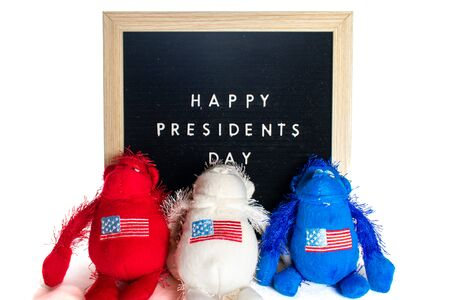 A Black Sign With White Letters That Says Happy Presidents Day With A Red, White, and Blue, Stuffed American Flag Monkey Stok Fotoğraf