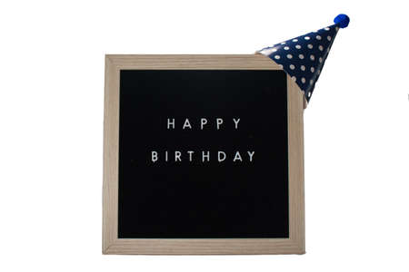 A Black Sign With a Birch Frame That Says Happy Birthday With a Dark Blue Polka-Dotted Birthday Hat and a Blue Cotton Ball on Top on a Pure White Background 版權商用圖片 - 151568872