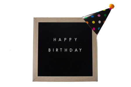 A Black Sign With a Birch Frame That Says Happy Birthday With a Black Polka-Dotted Birthday Hat and an Orange Cotton Ball on Top on a Pure White Background