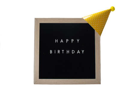 A Black Sign With a Birch Frame That Says Happy Birthday With a Yellow Birthday Hat and a Yellow Cotton Ball on Top on a Pure White Background
