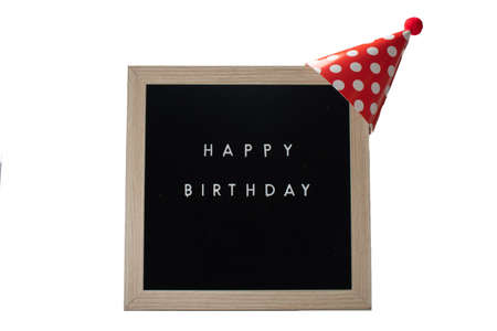 A Black Sign With a Birch Frame That Says Happy Birthday With a Red Polka-Dotted Birthday Hat and a Red Cotton Ball on Top on a Pure White Background 版權商用圖片