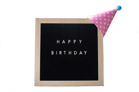 A Black Sign With a Birch Frame That Says Happy Birthday With a Pink Polka-Dotted Birthday Hat and a Light Blue Cotton Ball on Top on a Pure White Background 版權商用圖片