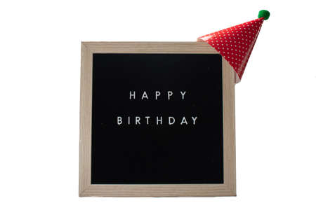 A Black Sign With a Birch Frame That Says Happy Birthday With a Red Birthday Hat and a Green Cotton Ball on Top on a Pure White Background