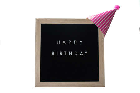 A Black Sign With a Birch Frame That Says Happy Birthday With a Pink Striped Birthday Hat and a Pink Cotton Ball on Top on a Pure White Background 版權商用圖片
