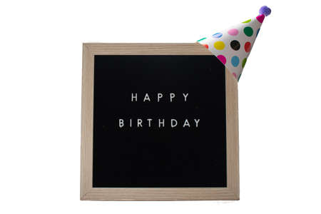 A Black Sign With a Birch Frame That Says Happy Birthday With a White Polka-Dotted Birthday Hat and a Purple Cotton Ball on Top on a Pure White Background 版權商用圖片 - 151568889
