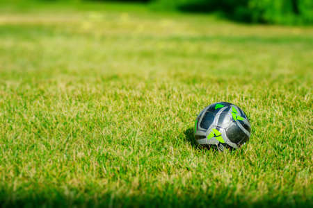 A Green and Black Soccer Ball in a Dreamy Grass Field During The Summer