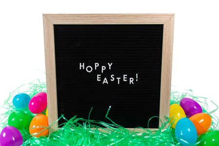 A Black Sign With a Birch Frame That Says Happy Easter in White Letters With Colorful Easter Eggs Scattered Behind It on a Pure White Background 版權商用圖片