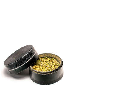 The Second Chamber of a Black and Used Grinder Full of Ground Marijuana on a Pure White Background 版權商用圖片 - 151902678