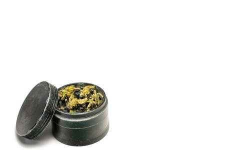 The Top Chamber of a Black and Used Grinder Full of Marijuana on a Pure White Background