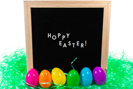 A Black Sign With a Birch Frame That Says Happy Easter in White Letters With a Set of Rainbow Eggs and Green Easter Grass in Front of It on a Pure White Background 版權商用圖片