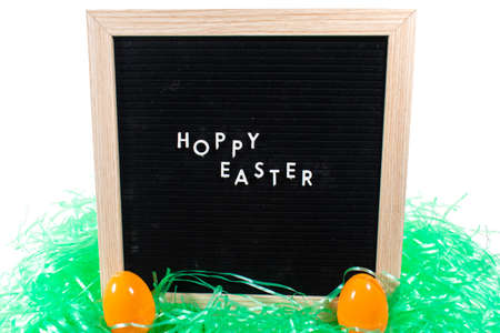 A Black Sign With a Birch Frame That Says Happy Easter in White Letters With Two Orange Easter Eggs and Green Easter Grass in Front of It on a Pure White Background 版權商用圖片