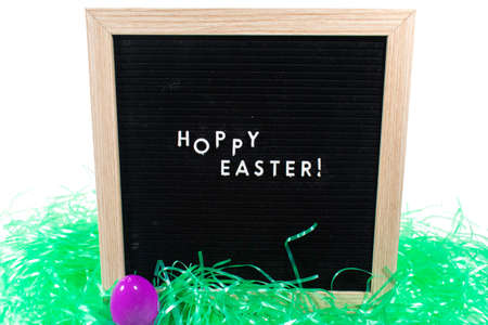 A Black Sign With a Birch Frame That Says Happy Easter in White Letters With a Purple Easter Egg and Green Easter Grass in Front of It on a Pure White Background