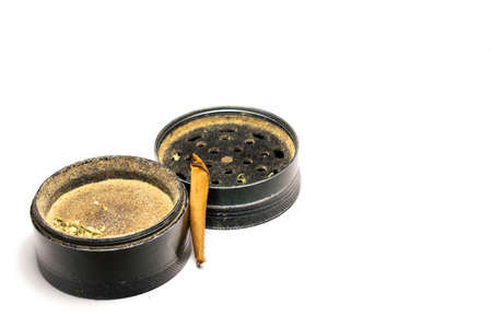 A Used Black Grinder With a Smoked Marijuana Cigar Next to It on a Pure White Background 版權商用圖片