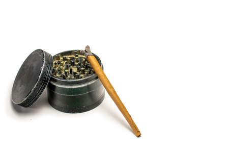 A Used Black Grinder With a Burning Marijuana Cigar Leaning On it On a Pure White Background
