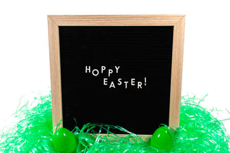 A Black Sign With a Birch Frame That Says Happy Easter in White Letters With Two Green Easter Eggs and Green Easter Grass in Front of It on a Pure White Background
