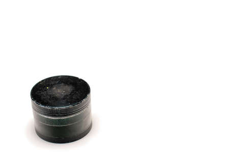 A Black and Used Marijuana Grinder With the Lid Tightly Closed