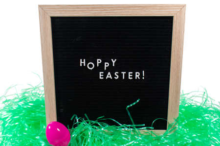 A Black Sign With a Birch Frame That Says Happy Easter in White Letters With a Pink Easter Egg and Green Easter Grass in Front of It on a Pure White Background 版權商用圖片 - 151902684