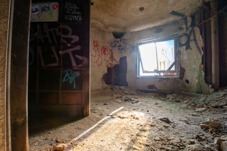 A Small Room in an Abandoned Building With Light Coming Through a Window and a Large Metal Door Covered in Graffiti