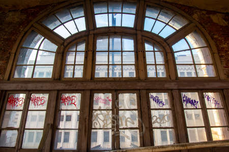 A Large and Detailed Arched Window in an Abandoned Building Covered in Graffiti 版權商用圖片