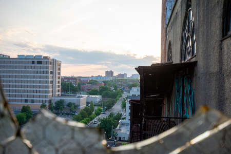 Looking Out a Broken Window in a Tall Abandoned Building at a Busy City Street and Skyline