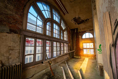 A Small Room in an Abandoned Building With a Large and Detailed Arched Window Covered in Graffiti 版權商用圖片 - 152373742